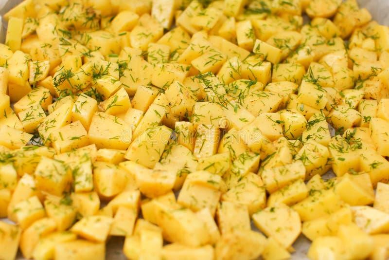 关闭在选择聚焦切开了与调味料和莳萝的土豆在一个盘子 免版税库存照片