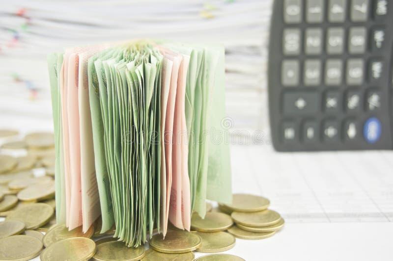 关闭在金币的堆票据 免版税库存照片