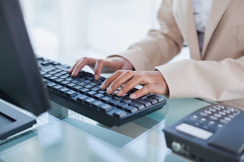 关闭在键入在她的键盘的女实业家 免版税图库摄影