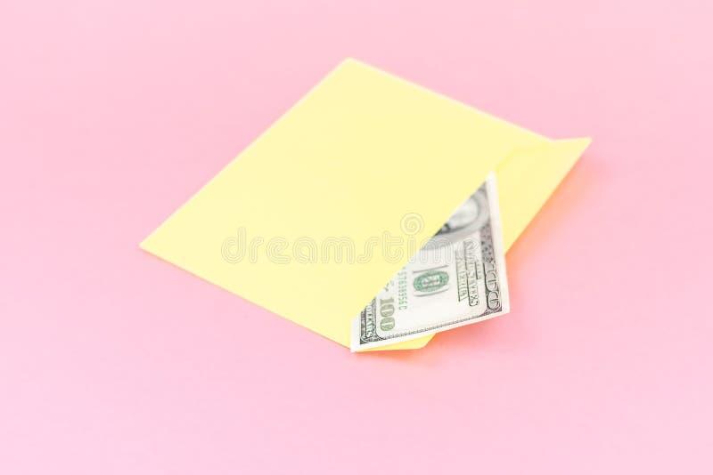 关闭在黄色信封的金钱说谎在粉红彩笔背景 烙记的嘲笑;正面图 库存图片
