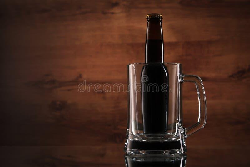 关闭在玻璃杯子的啤酒瓶 免版税库存图片