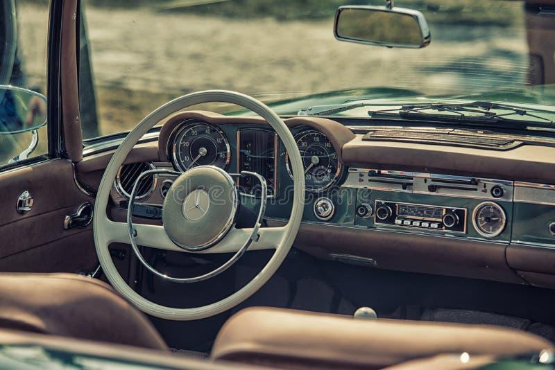 关闭在默西迪丝葡萄酒汽车方向盘和驾驶舱 图库摄影