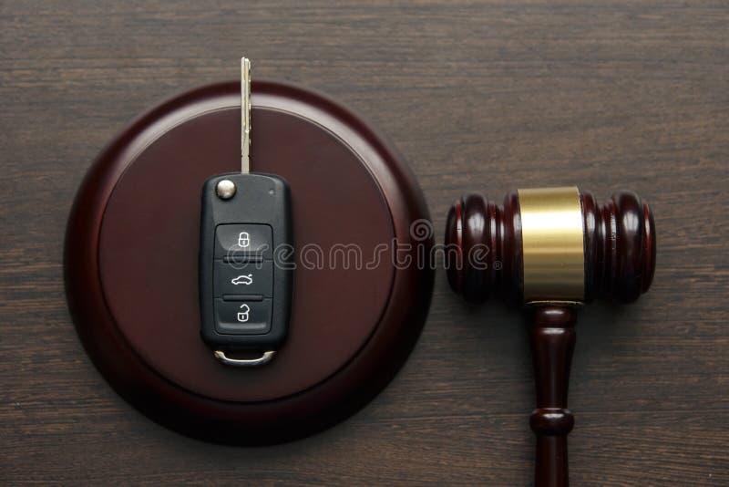 关闭在soundboard的木法官惊堂木和汽车钥匙在白色背景 库存图片