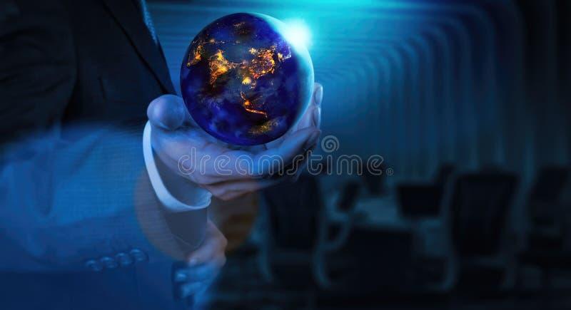 关闭地球在晚上停滞在地球日和节能概念的商人手上 免版税库存图片