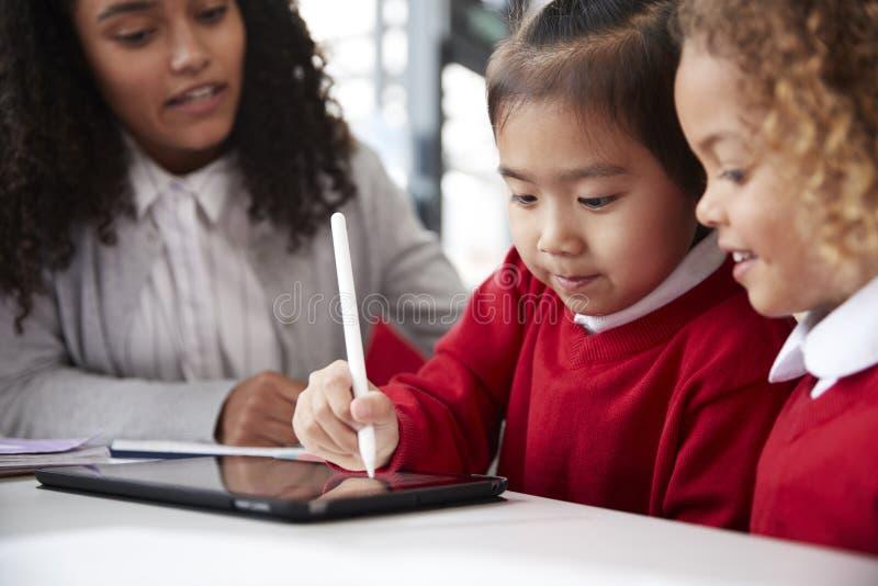 关闭坐在一张书桌的女性婴儿学校老师在帮助两位女小学生的教室穿校服使用a 免版税库存图片