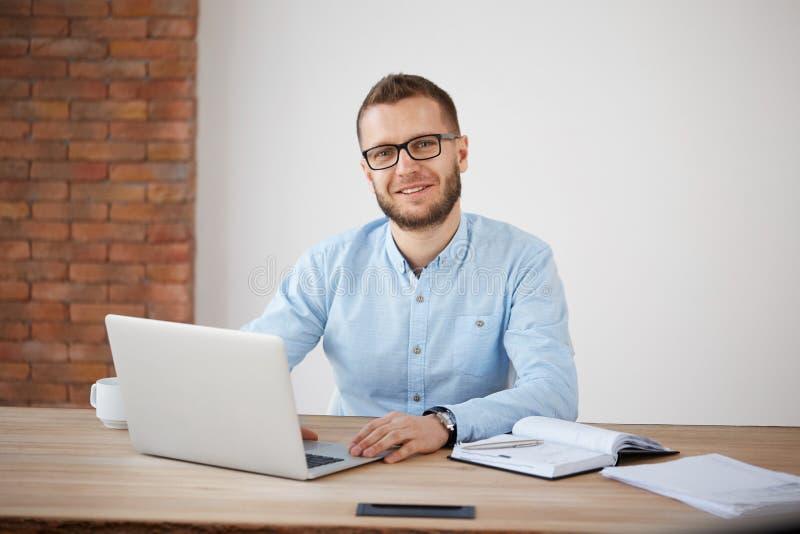 关闭坐在书桌的玻璃和经典衬衣的快乐的成人有胡子的男性经理在办公室,工作在 库存照片