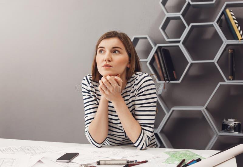 关闭坐在共同工作的空间的桌上的美丽的年轻欧洲深色头发的女性设计师画象,看 免版税库存照片