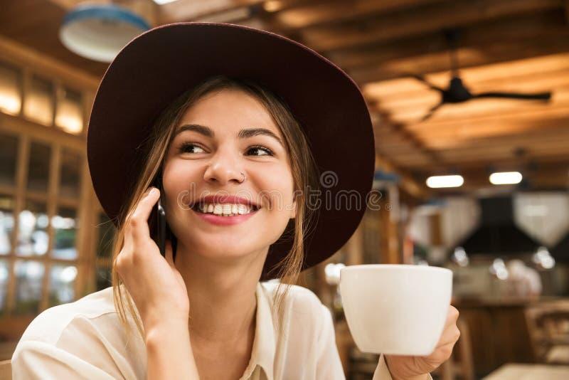 关闭坐在咖啡馆桌上的帽子的一个愉快的可爱的女孩户内,拿着茶, 库存照片