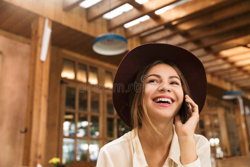 关闭坐在咖啡馆桌上的帽子的一个笑的女孩户内, 免版税库存图片