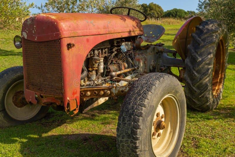 关闭坐在庭院里的一台生锈的红色拖拉机 库存照片