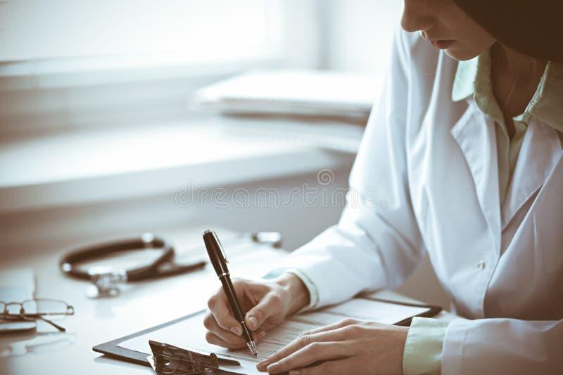 关闭坐在桌上的未知的女性医生靠近窗口在医院 库存照片