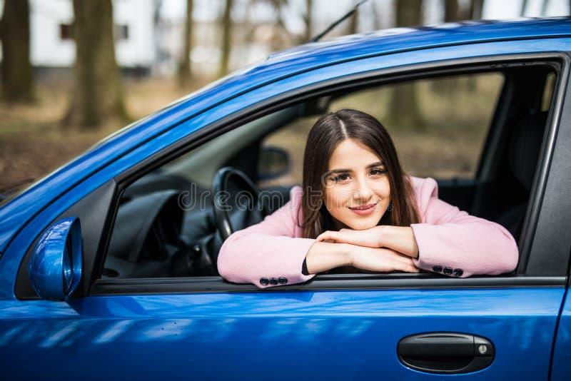 关闭坐在从车窗的汽车微笑愉快的心情的少妇室外生活方式旅行照片 免版税库存照片