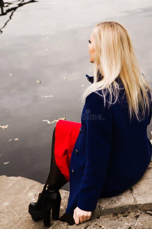 关闭坐由河的妇女 免版税库存照片