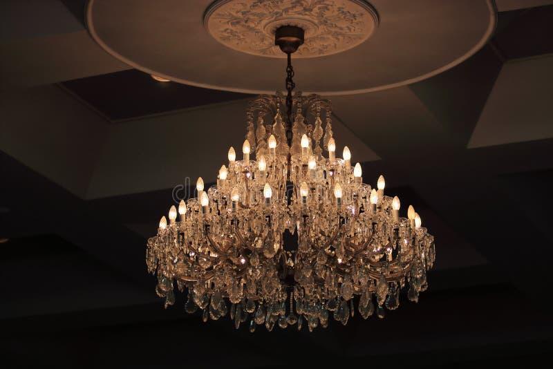 关闭垂悬在天花板下的豪华水晶枝形吊灯在屋子里 库存照片