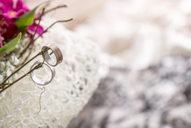 关闭垂悬在新娘花束的枝杈的两个婚戒 免版税库存图片