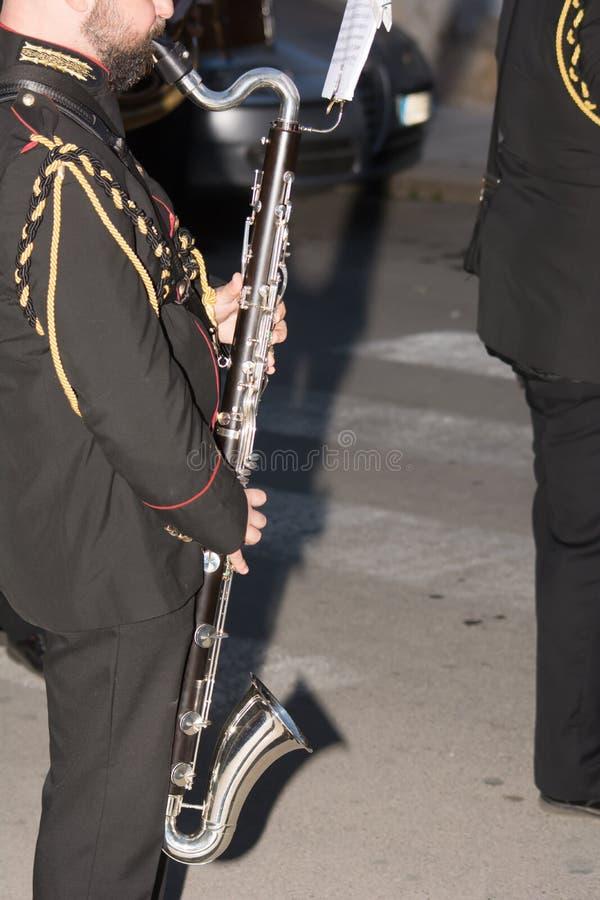 关闭垂直的看法演奏在B的音乐家低音笛 库存图片