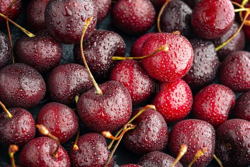 关闭堆与茎的成熟樱桃 新鲜的红色樱桃的大收藏量 成熟樱桃背景 免版税库存照片