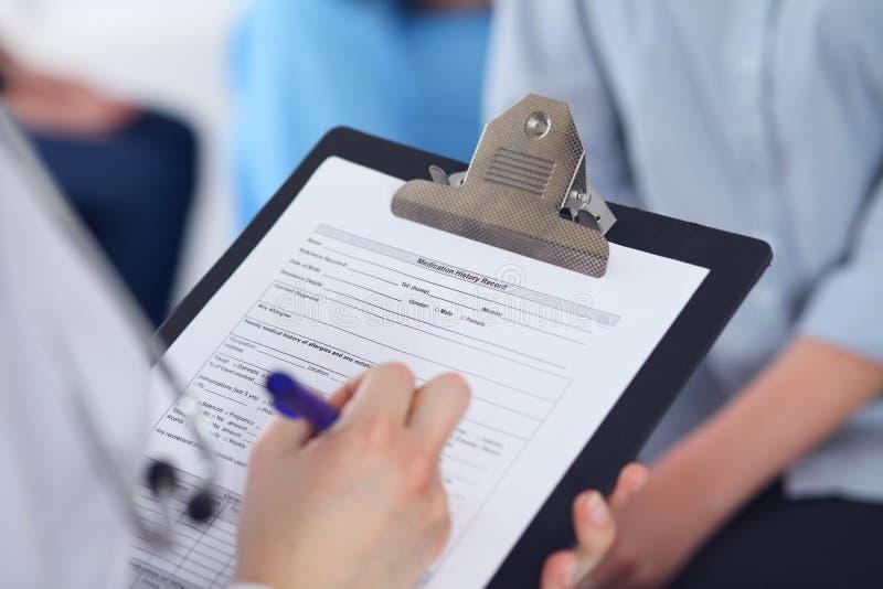 关闭填好申请表的一位女性医生,当谈话与患者时 医学和医疗保健概念 免版税库存图片