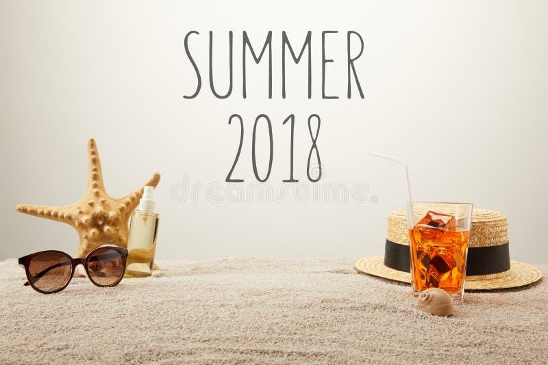 关闭夏天2018年字法、鸡尾酒与冰,草帽、太阳镜和晒黑的油看法在沙子在灰色背景 库存照片