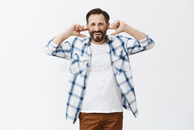 关闭大声的音乐,它是讨厌的 在便衣的生气的不快乐的成熟欧洲男性,盖耳朵用索引 免版税库存照片