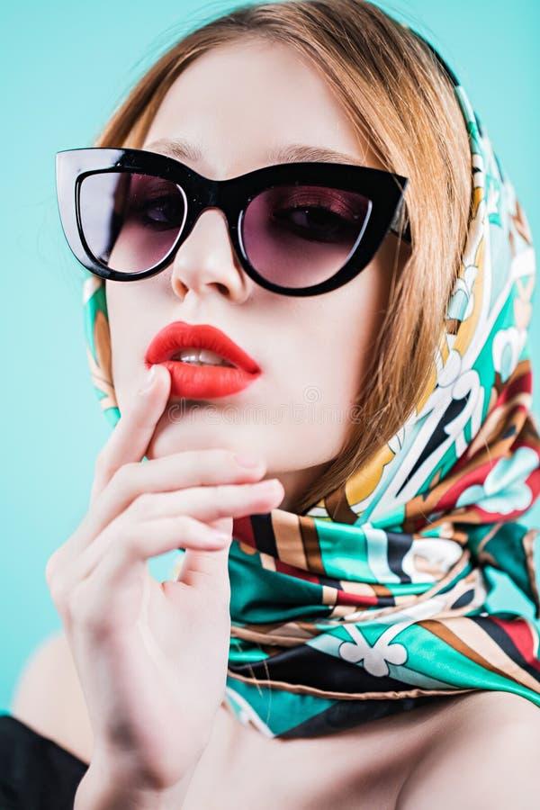 关闭太阳镜的微笑反对蓝色背景的时髦的少妇射击  免版税库存图片