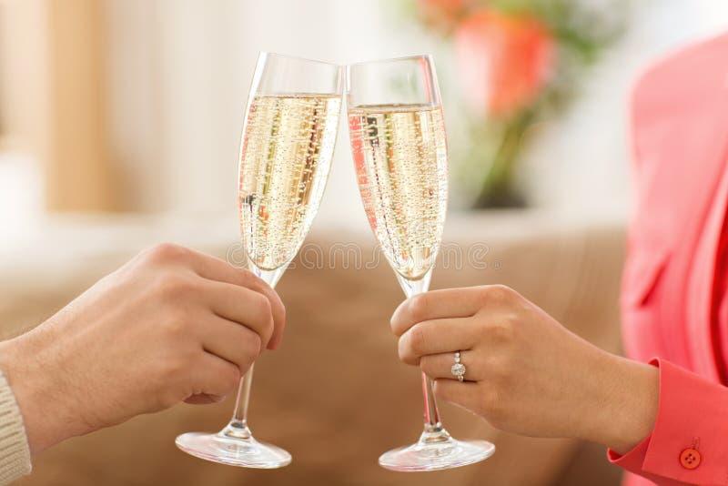关闭夫妇使叮当响的香槟玻璃 免版税库存图片