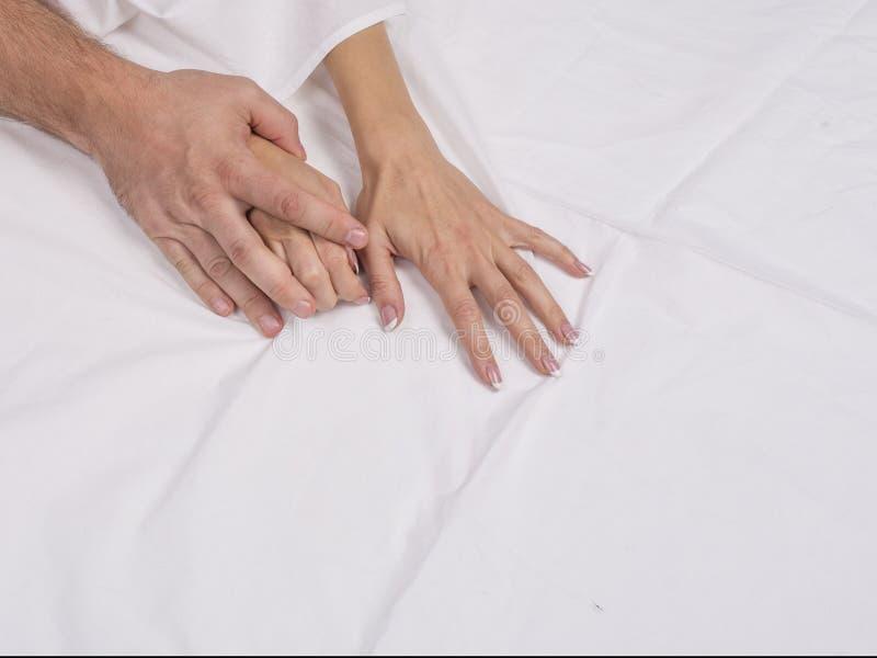 关闭夫妇手在床上说谎在卧室,恋人有强烈的性或做爱感觉性交高潮和满意 免版税库存照片