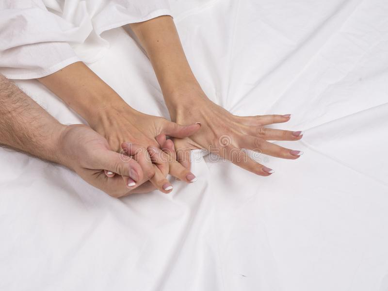 关闭夫妇手在床上说谎在卧室,恋人有强烈的性或做爱感觉性交高潮和满意 图库摄影