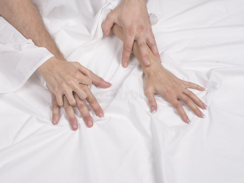 关闭夫妇手在床上说谎在卧室,恋人有强烈的性或做爱感觉性交高潮和满意 库存照片
