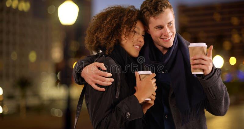 关闭夫妇饮用的咖啡画象在晚上 免版税库存照片