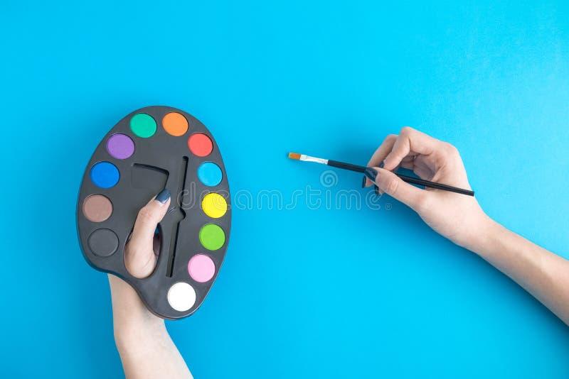 关闭女性举行的在蓝色隔绝的油漆调色板和刷子 免版税库存图片