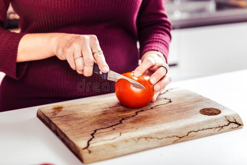 关闭女性手切蕃茄 库存照片