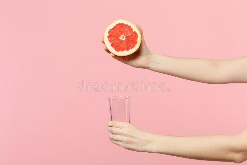 关闭女性藏品播种的照片手一半的新鲜的成熟葡萄柚,在桃红色淡色墙壁上隔绝的玻璃杯子 免版税库存图片