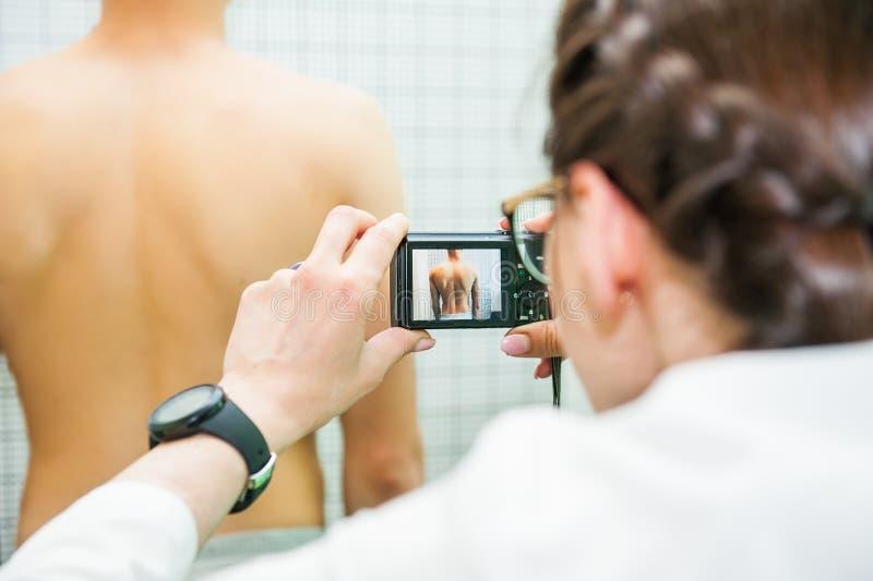 关闭她的实践的女性生理治疗师,做照片写真男性pacient ` s后面 免版税图库摄影
