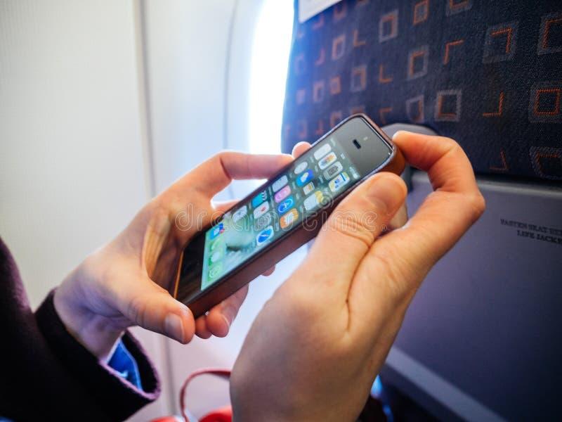 关闭她的手机智能手机平面飞机的妇女 免版税库存照片