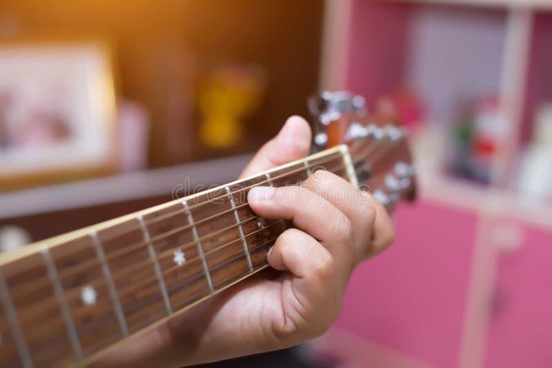 关闭妇女在公园实践吉他的年轻行家,愉快并且喜欢弹吉他 免版税库存照片
