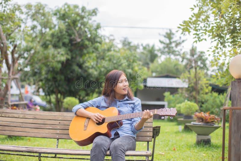 关闭妇女在公园实践吉他的年轻行家,愉快并且喜欢弹吉他 库存照片