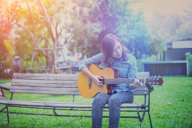 关闭妇女在公园实践吉他的年轻行家,愉快并且喜欢弹吉他 免版税图库摄影