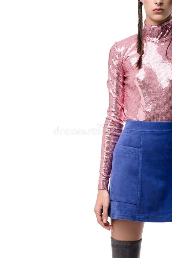 关闭妇女在蓝色裙子的身体身分和与衣服饰物之小金属片的桃红色上面在白色背景 免版税库存照片