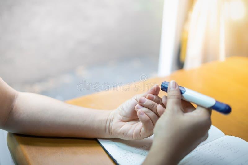 关闭妇女手使用在手指的柳叶刀由葡萄糖米检查血糖水平与年计划者预定 ??  库存照片