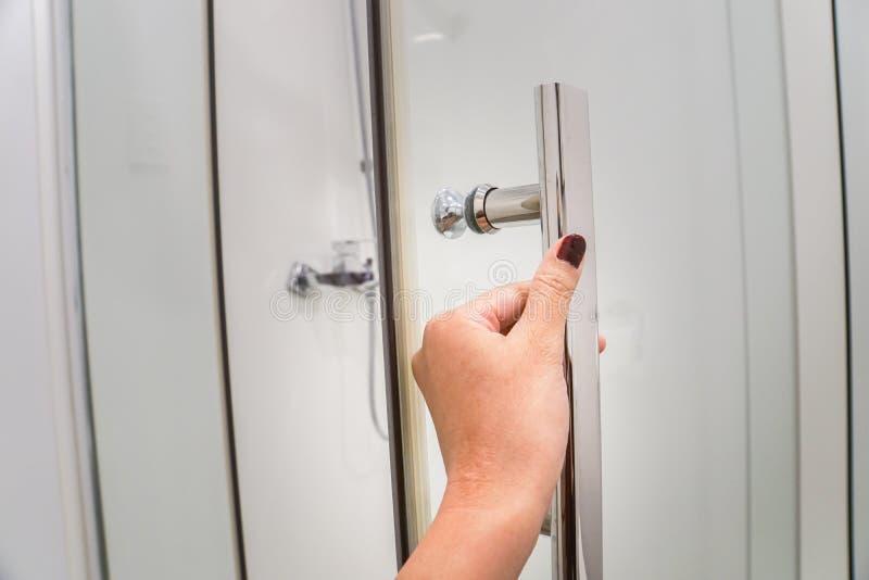 关闭妇女手拉扯阵雨门在豪华卫生间里 库存照片