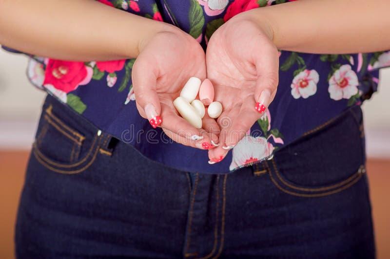 关闭妇女手,拿着在她的开放手上软的明胶阴道片剂或塞剂,疾病的治疗 库存图片