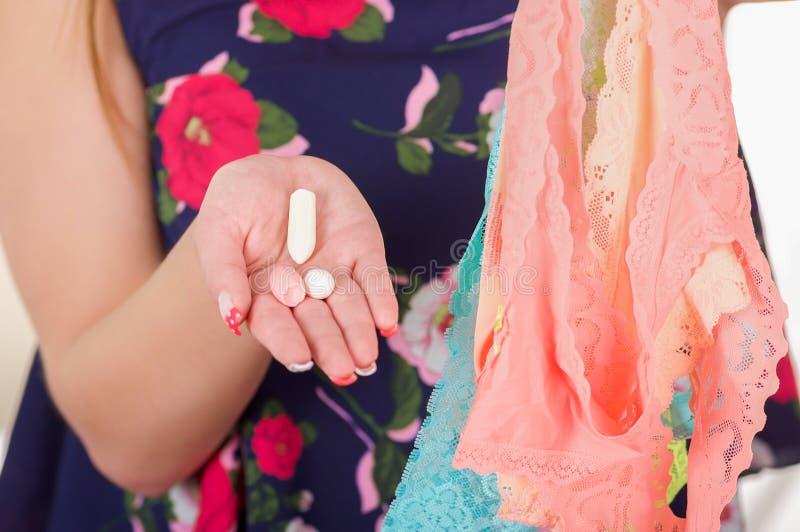关闭妇女手,拿着被分类的五颜六色的内衣和软的明胶阴道片剂或者塞剂 免版税图库摄影