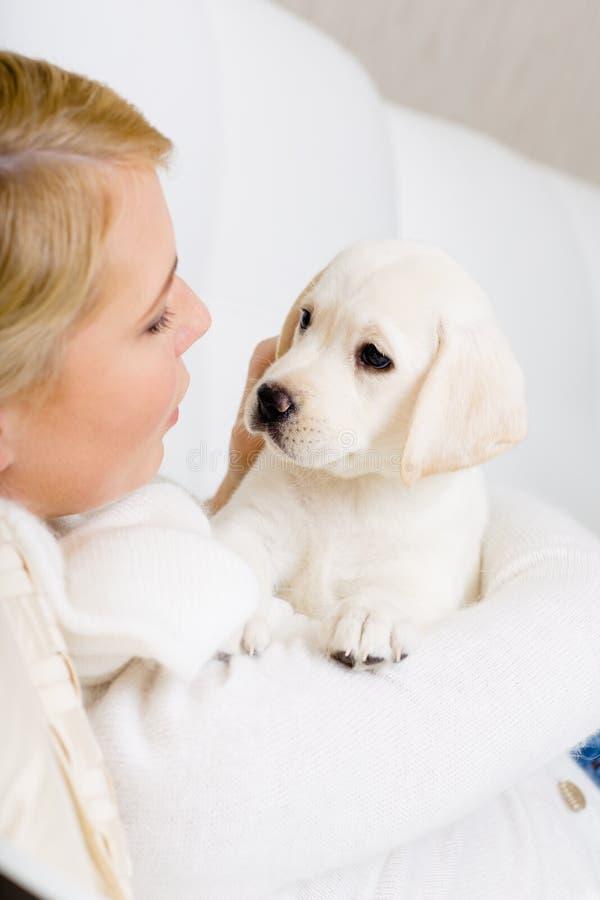 关闭妇女拥抱白色小狗 免版税库存图片