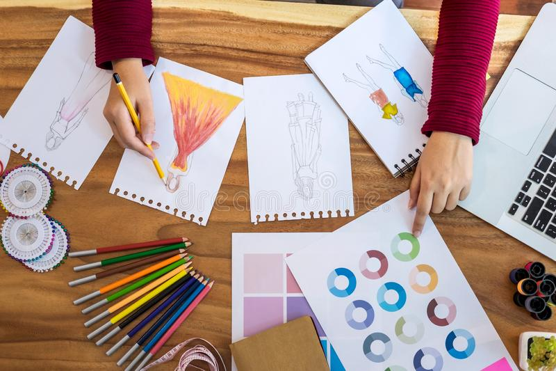 关闭妇女时尚编辑在衣裳的工作画的剪影在有裁缝工具和颜色图表的,行业工作室 免版税库存照片