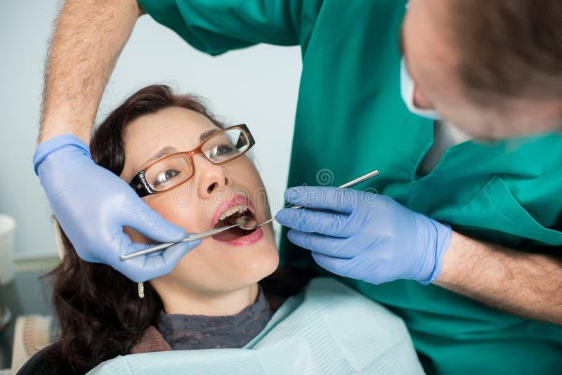 关闭妇女有牙齿检查在牙齿办公室 牙医有牙齿的审查的患者` s牙 免版税库存图片