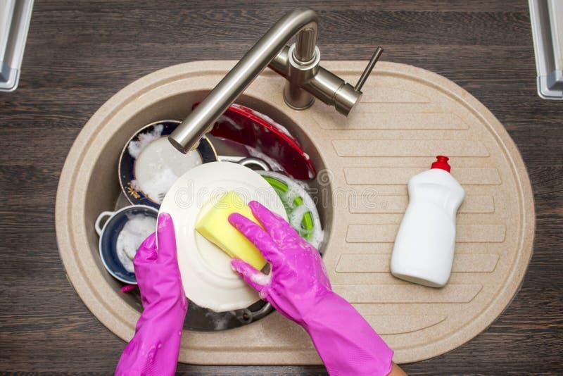 关闭妇女洗碗的手在厨房里 在洗盘子的红色橡胶手套的手 r 免版税图库摄影