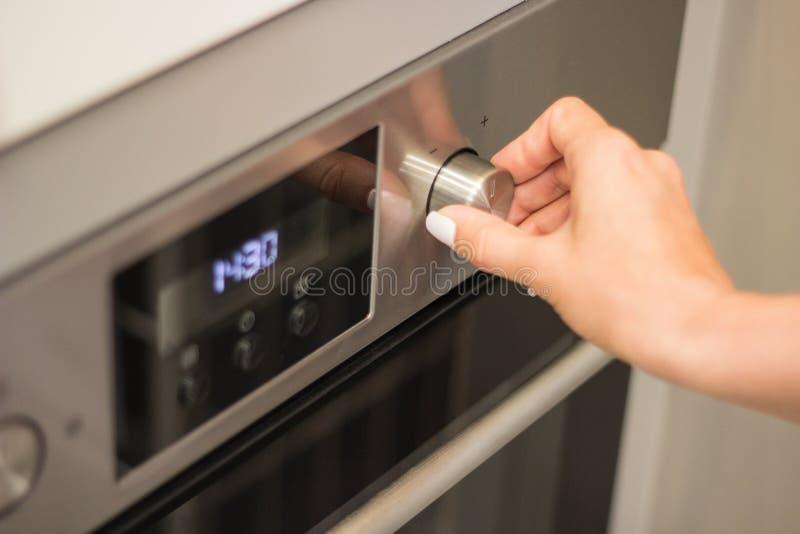 关闭妇女烹调方式或温度在烤箱的手设置 免版税库存照片