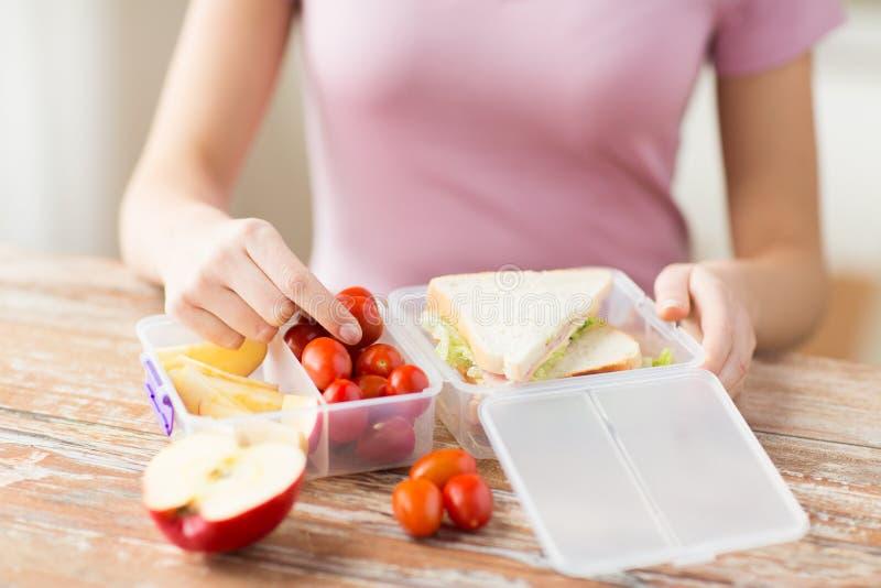 关闭妇女用在塑胶容器的食物 库存照片