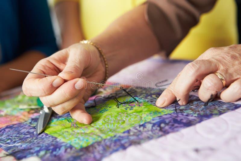 关闭妇女的手缝合的被子 免版税库存照片